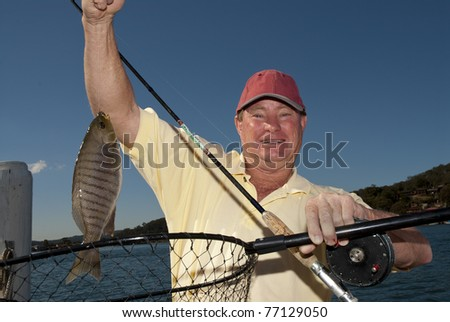 Man holds up his black fish catch - stock photo