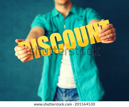 Man holds word Discount on bright colorful background