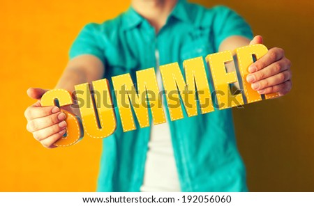 Man holds word Summer on bright colorful background