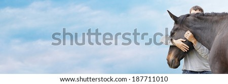 Man hugging his black horse's head against  sky , banner                  - stock photo