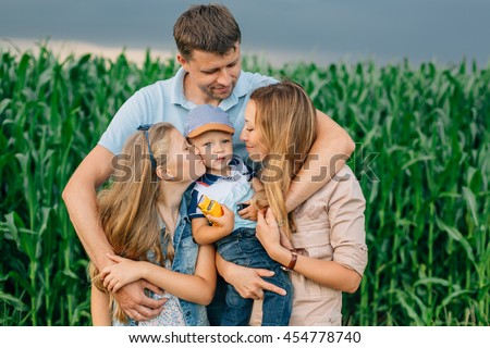 Man hugging his wife, daughter and little son.Cute happy family in front of cornfield and thunder sky. Sister kissing her brother - stock photo