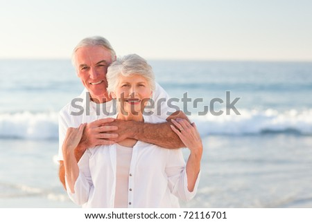 Man hugging his wife on the beach - stock photo