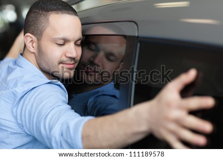 Man hugging on a car in a car dealership - stock photo