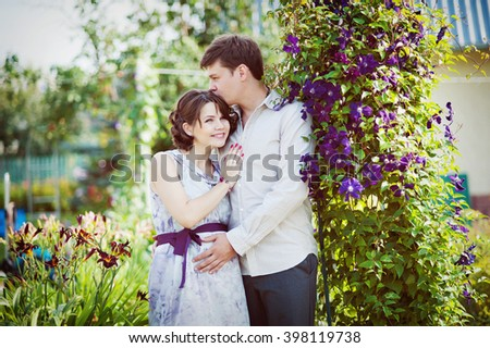 Man hugging pregnant wife about flowering plants.