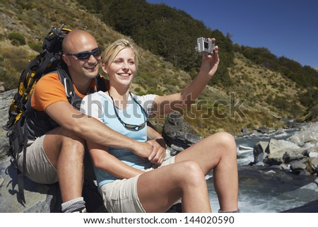 Man hugging woman as she takes their picture by river in the forest - stock photo