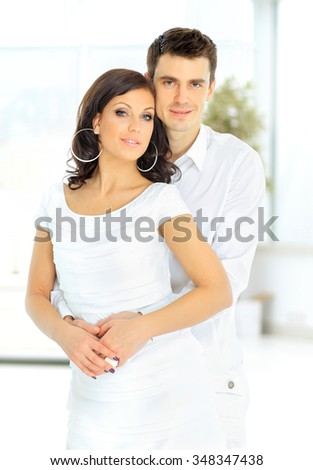 man hugs a woman looking at the camera - stock photo