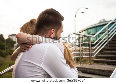 man hugs his woman on modern staircases - stock photo