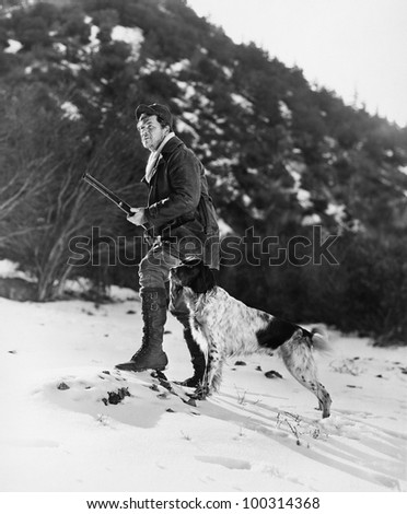 Man hunting in snowy mountains with dog - stock photo