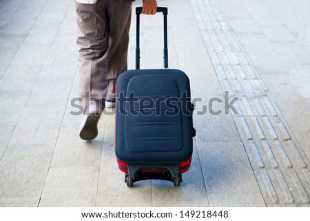 man hurry walk with suitcase in terminal - stock photo