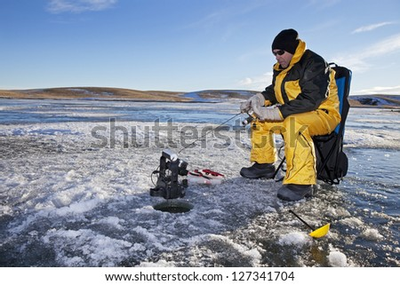 Man ice fishing on a frozen Canadian lake. - stock photo