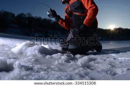 Man ice fishing on a lake in winter - stock photo