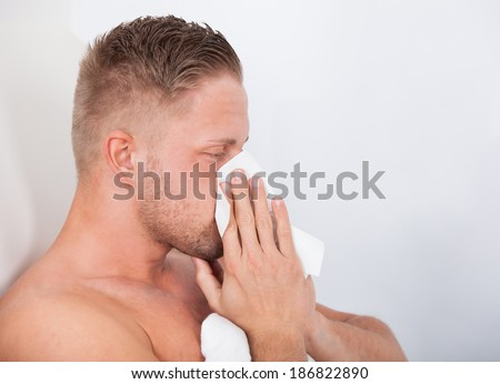 Man ill in bed with a seasonal cold or influenza blowing his nose on a tissue  side view close up - stock photo