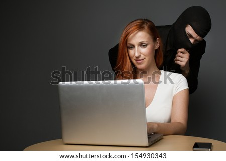 Man in a balaclava furtively watching an unsuspecting female office worker working on her laptop computer while corporate spying, stealing personal or business information or employee monitoring
