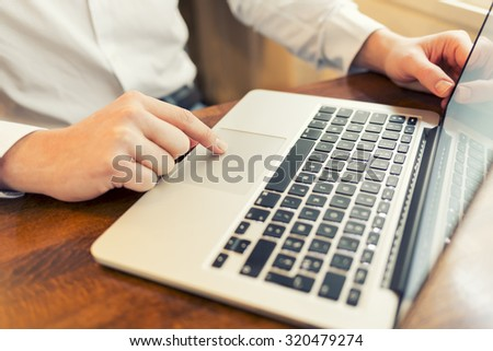 Man in a bar working on laptop. Vintage filter - stock photo