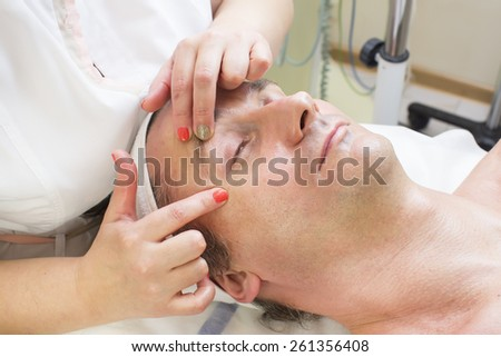 man in a beauty salon facial and massage - stock photo