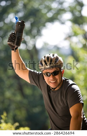Man in a bicycle raising hand - stock photo