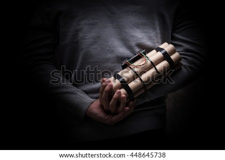 man in a black jacket strapped with explosives and detonator holds in hand - stock photo
