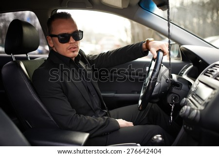 man in a black suit sitting behind the wheel - stock photo