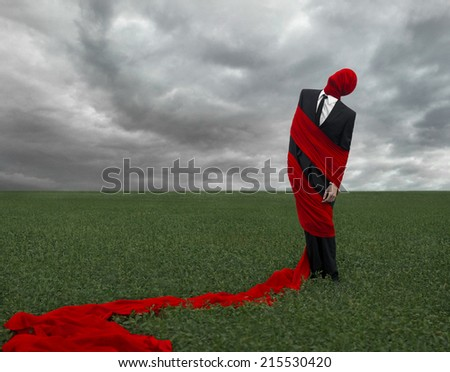 Man in a black suit with a red cloth is in the green field, loneliness, dreams, sleep, red fabric, storm clouds - stock photo