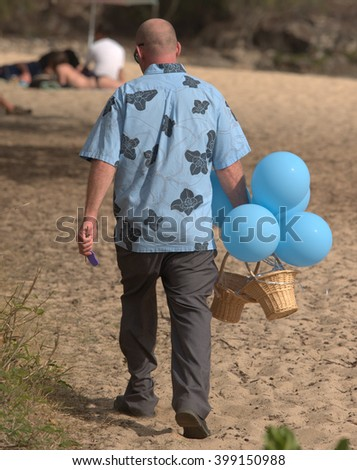 Man in a blue Hawaiian shirt carrying a basket and balloons heads across a beach - stock photo