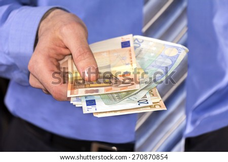 Man in a blue shirt, Pay in Euros banknotes - stock photo