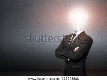 Man in a business suit stands, behind him empty concrete wall. Instead of head businessman lighting bulb. Business, idea concept. - stock photo