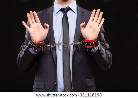 man in a business suit with chained hands. handcuffs for sex games - stock photo