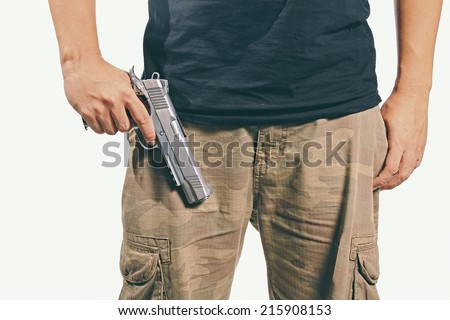 Man in a camouflage pants holding a gun, Army, Semi-automatic handgun, 45 pistol. (Color Process)