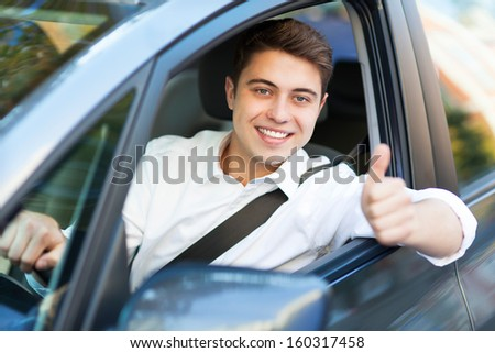 Man in a car with thumbs up - stock photo
