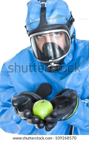 Man in a chemical suit and gas mask holding contaminated apple - isolated white background - stock photo