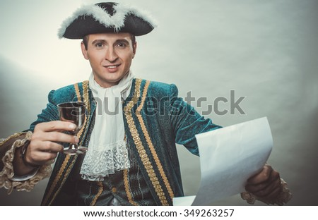 Man in a cocked hat is holding a glass and paper
