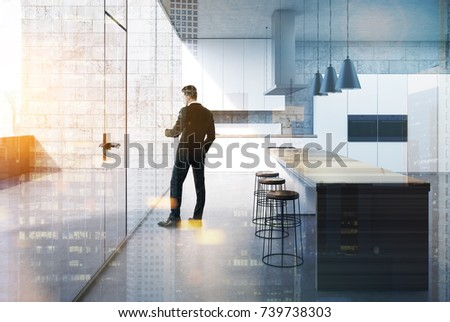 Man in a concrete kitchen interior with a concrete floor, white cabinets and consoles with built in cookers and a balcony. A bar stand with wooden stools. 3d rendering