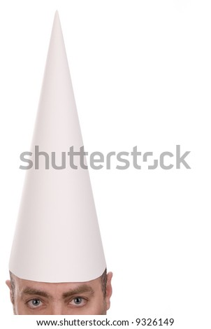 Man in a dunce cap over a white background - stock photo