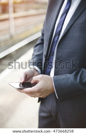 Man in a formal business suit using a smartphone outdoors. Only his torso is in the shot.