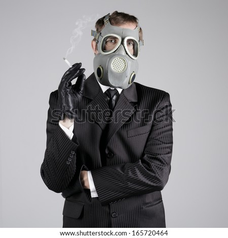 Man in a gas mask with a cigarette - stock photo
