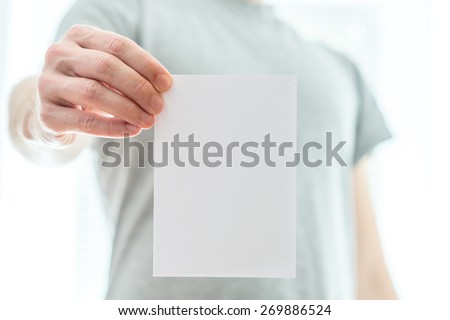 Man in a grey t-shirt holding a blank white piece of paper in his extended hand with copyspace for your text or advertisement. - stock photo