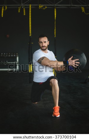 man in a gym exercising with a ball. Dark background