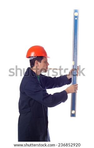 man in a helmet and  blue robe holding building level, pensil in mouth, turned sideways - stock photo