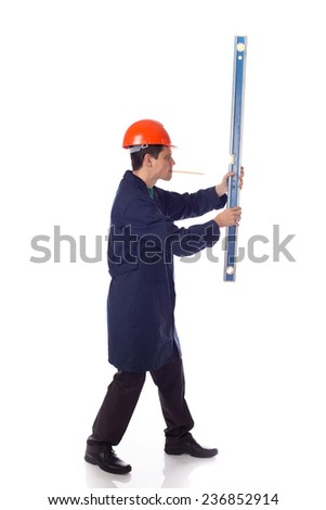 man in a helmet and  blue robe holding holding level, pensil in mouth, turned sideways - stock photo