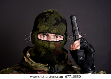 man in a mask holding gun - stock photo