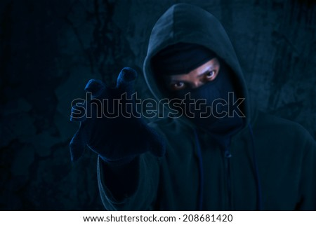 Man in a mask showing hand to attack - stock photo