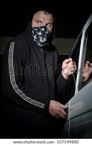 Man in a mask trying to steal car - stock photo