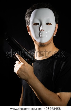 Man in a Mask with a Gun in isolated Black Background - stock photo