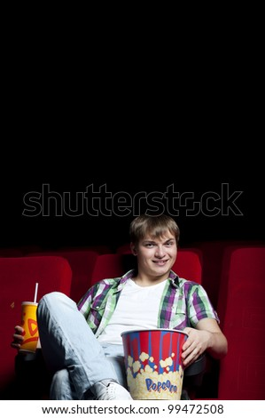 man in a movie theater, watching a movie and drink a drink - stock photo