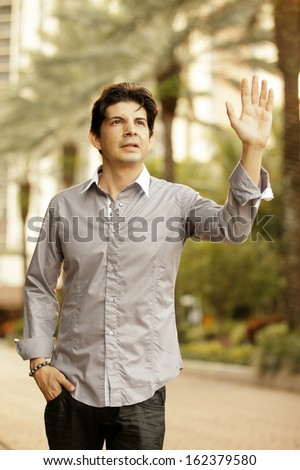 Man in a nature setting waving - stock photo
