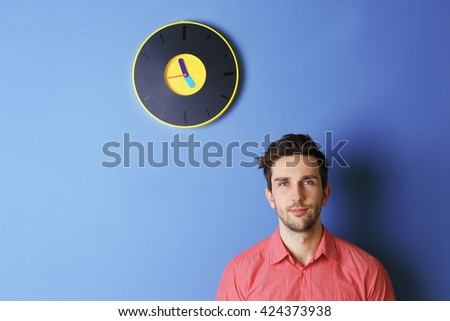 Man in a pink shirt standing beside a  big clock on blue wall - stock photo