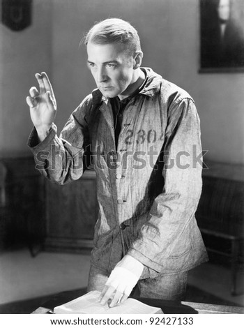 Man in a prisoners garb holding up his fingers swearing an oath - stock photo