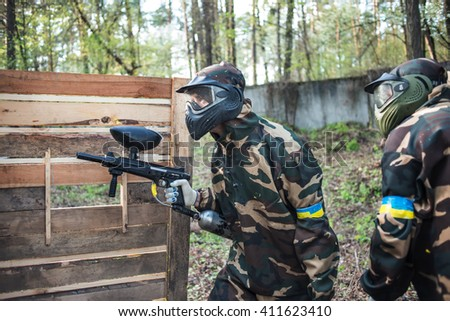 Man in a protective mask with a gun to play paintball in the woods in summer - stock photo