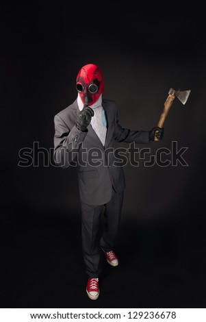 Man in a red mask handmade with axe on a black background - stock photo