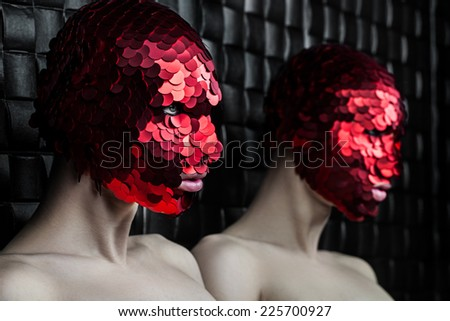 Man in a red mask near the mirror in the room